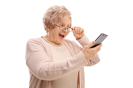 Photo for Excited senior looking at a phone isolated on white background - Royalty Free Image