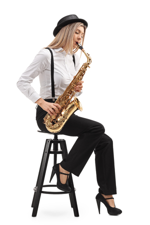 Photo for Female jazz musician seated on a chair playing a saxophone isolated on white background - Royalty Free Image