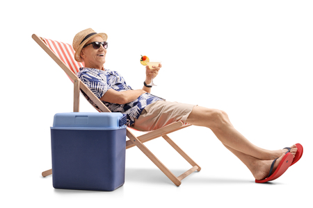 Photo pour Elderly tourist with a cocktail sitting in a deck chair next to a cooling box isolated on white background - image libre de droit
