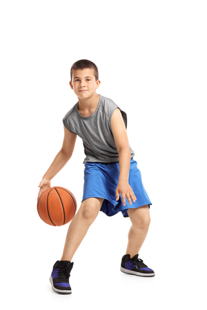 Photo pour Full length portrait of a kid playing with a basketball isolated on white background - image libre de droit
