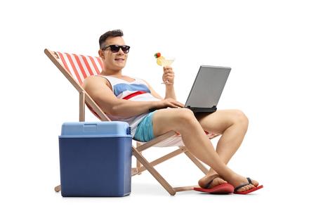 Foto de Young man with a laptop and a cocktail sitting in a deck chair next to a cooling box isolated on white background - Imagen libre de derechos