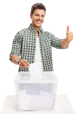 Foto de Young man voting and making a thumb up sign isolated on white background - Imagen libre de derechos