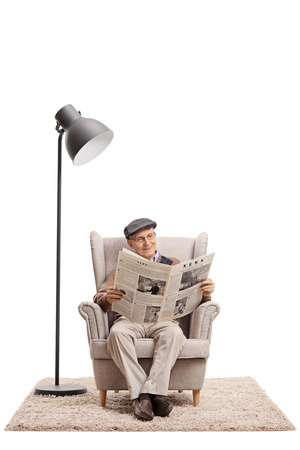 Foto de Elderly man reading a newspaper in an armchair next to a lamp isolated on white background - Imagen libre de derechos