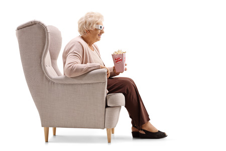 Foto de Mature woman with a box of  popcorn and 3D glasses seated in an armchair isolated on white background - Imagen libre de derechos