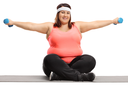 Foto de Overweight woman seated on an exercise mat exercising with small dumbbells isolated on white background - Imagen libre de derechos