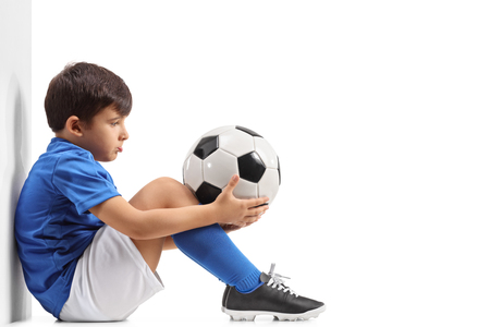 Photo for Disappointed little footballer leaning against a wall isolated on white background - Royalty Free Image
