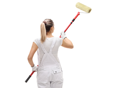 Photo for Rear shot of a female painter painting with a paint roller isolated on white background - Royalty Free Image