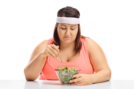 Foto de Sad overweight woman sitting at a table and looking at a bowl of salad isolated on white background - Imagen libre de derechos
