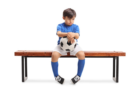 Foto für Sad little footballer sitting on a wooden bench isolated on white background - Lizenzfreies Bild
