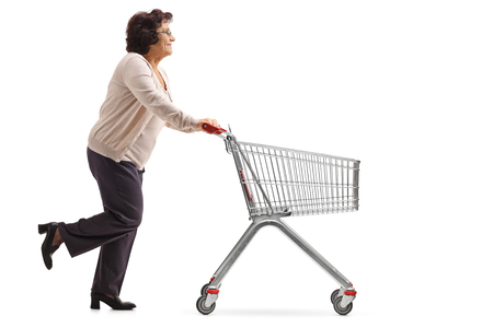 Foto de Full length profile shot of an elderly woman running and pushing an empty shopping cart isolated on white background - Imagen libre de derechos