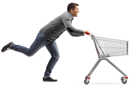 Foto de Full length profile shot of a guy running and pushing an empty shopping cart isolated on white background - Imagen libre de derechos