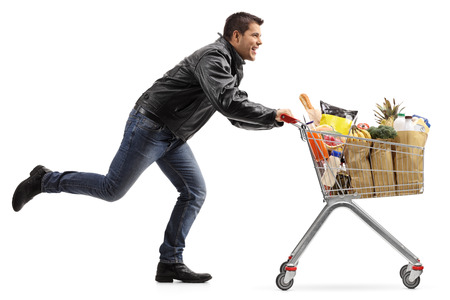 Photo for Full length profile shot of a biker running and pushing a shopping cart filled with groceries isolated on white background - Royalty Free Image