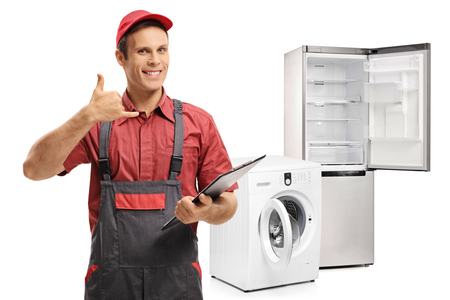 Photo pour Repairman with a clipboard making a call me gesture in front of a washing machine and a fridge isolated on white background - image libre de droit