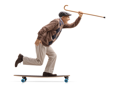 Foto de Full length profile shot of a joyful senior holding a cane and riding a longboard isolated on white background - Imagen libre de derechos
