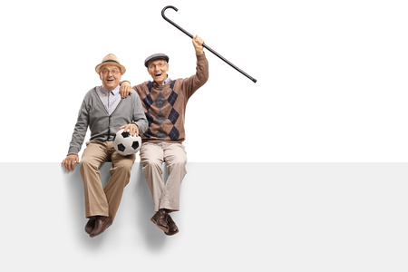 Photo for Cheerful seniors with a football seated on a panel isolated on white background - Royalty Free Image