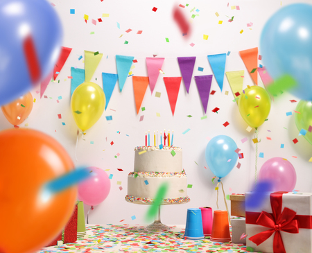 Photo pour Birthday cake with burning candles against a wall with decoration flags - image libre de droit