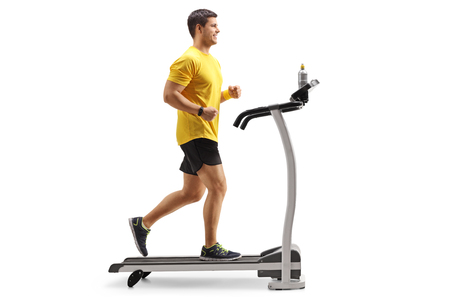 Photo pour Full length profile shot of a young man running on a treadmill isolated on white background - image libre de droit