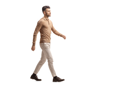Foto de Full length profile shot of a young man walking isolated on white background - Imagen libre de derechos