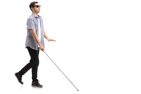 Photo pour Full length profile shot of a blind young man with a cane walking isolated on white background - image libre de droit