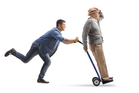 Foto de Full length profile shot of a young man pushing a hand truck with a mature man riding on it isolated on white background - Imagen libre de derechos