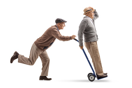 Foto de Full length profile shot of a senior pushing a hand truck with another senior riding on it isolated on white background - Imagen libre de derechos