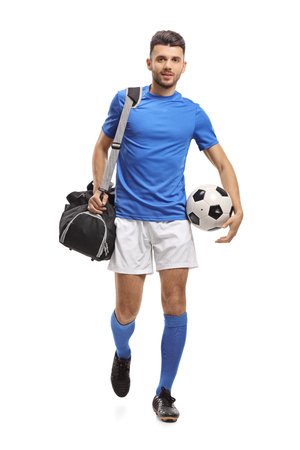 Photo for Full length portrait of a soccer player with a bag and a football walking towards the camera isolated on white background - Royalty Free Image