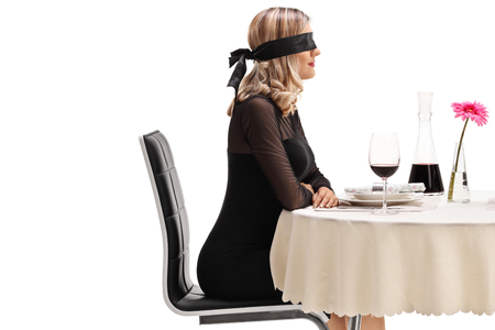 Photo pour Young woman wearing a blindfold sitting at a restaurant table isolated on white background - image libre de droit
