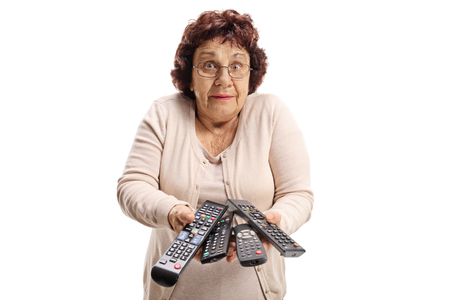 Photo for Confused elderly woman with remote controls isolated on white background - Royalty Free Image