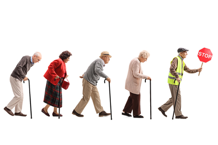 Photo pour Full length shot of senior people walking in a line behind an elderly man with a safety vest and stop sign isolated on white background - image libre de droit
