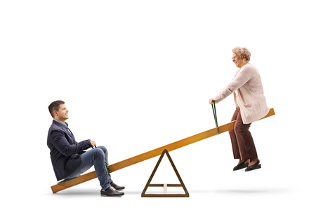 Photo pour Young guy and an elderly woman on a seesaw isolated on white - image libre de droit