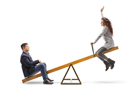 Photo pour Young couple on a seesaw isolated on white - image libre de droit