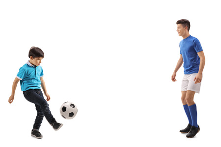 Foto de Full length shot of a little boy playing soccer with an older boy isolated on white background - Imagen libre de derechos