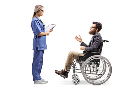 Photo pour Full length profile shot of a young female nurse talking to a bearded man in a wheelchair isolated on white background - image libre de droit