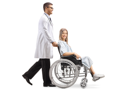 Photo for Full length shot of a young male doctor pushing a female patient in a wheelchair isolated on white background - Royalty Free Image
