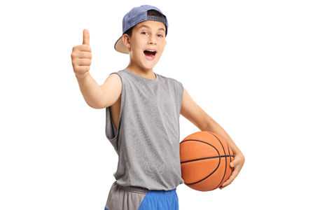 Photo pour Cool teenage boy with a basketball showing thumbs up isolated on white background - image libre de droit
