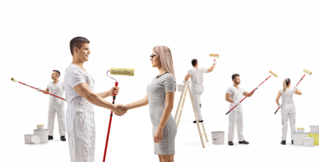 Foto de Full length profile shot of a male painter shaking hands with a young woman and workers painting wall isolated on white background - Imagen libre de derechos