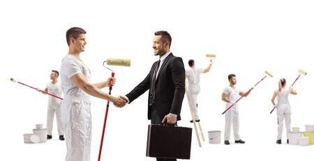 Foto de Full length profile shot of a painter shaking hands with a businessman and workers painting isolated on white background - Imagen libre de derechos
