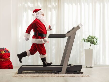 Foto per Full length profile shot of Santa Claus running on a treadmill at home - Immagine Royalty Free