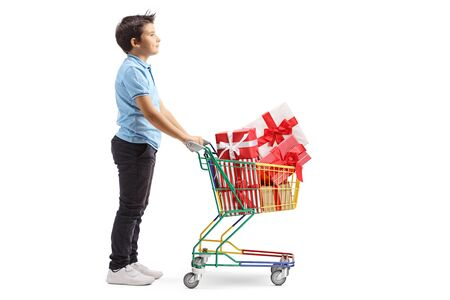 Foto de Full length profile shot of a boy with a shopping cart full of wrapped presents isolated on white background - Imagen libre de derechos
