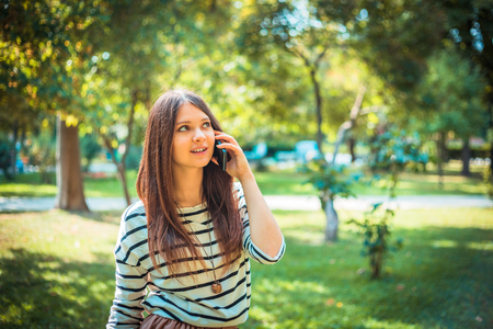 Photo for Beautiful young woman talking on a phone in city park. - Royalty Free Image