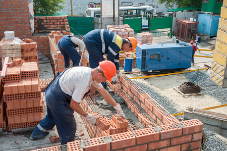 Foto de Tyumen, Russia - July 31, 2013: JSC Mostostroy-11. Construction of a 18-storeyed brick residental house at the intersection of streets of Nemtsov and Tsiolkovsky. Team of bricklayers behind work - Imagen libre de derechos