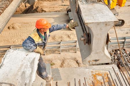 Photo pour Tyumen, Russia - July 31, 2013: JSC Mostostroy-11. Bridge construction for outcome of the Tobolsk path and Bypass road round Tyumen. Builder mount bridge span - image libre de droit
