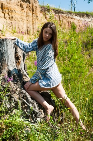 Photo for Portrait of young attractive brunette woman standing on stump - Royalty Free Image