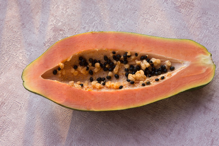 Photo for Papaya (Carica papaya) is an exotic, tasty, sweet fruit. Melon (bread) tree fruit against a pink background. Half. Papaya seeds are edible and can be a cure. Close-up. - Royalty Free Image