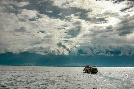 Photo pour A boat advances on Lake Erhai towards the city of Dali while the clouds cling to the surrounding mountains - image libre de droit