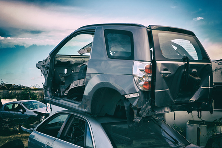 Foto de Car recycling. Dump of old cars after an accident on the road. Industrial scrap - Imagen libre de derechos