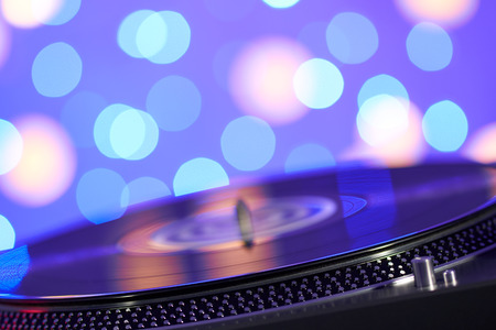 Foto de Turntable vinyl record player. Sound technology for DJ to mix & play music. Vintage vinyl record player on a background decorations for a party, bright disco lights. Needle on a vinyl record - Imagen libre de derechos