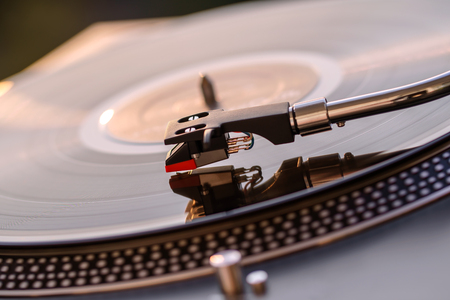 Foto für Turntable vinyl record player on the background of a sunset over the lights city. Sound technology for DJ to mix & play music. Black vinyl record. Vintage vinyl record player. Needle on a vinyl record - Lizenzfreies Bild