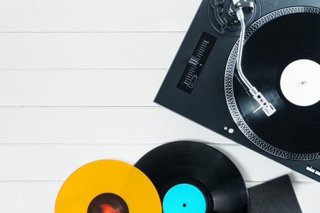 Photo for Festive postcard frame.Turntable vinyl record player on the background of their white wooden boards. Sound technology for DJ to mix & play music. Red, black, violet vinyl records - Royalty Free Image
