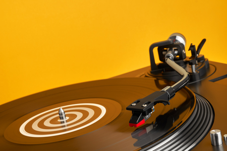 Photo pour Turntable vinyl record player. Sound technology for DJ to mix & play music. Vinyl record player on a yellow background decorations for a party, bright disco lights. Need - image libre de droit